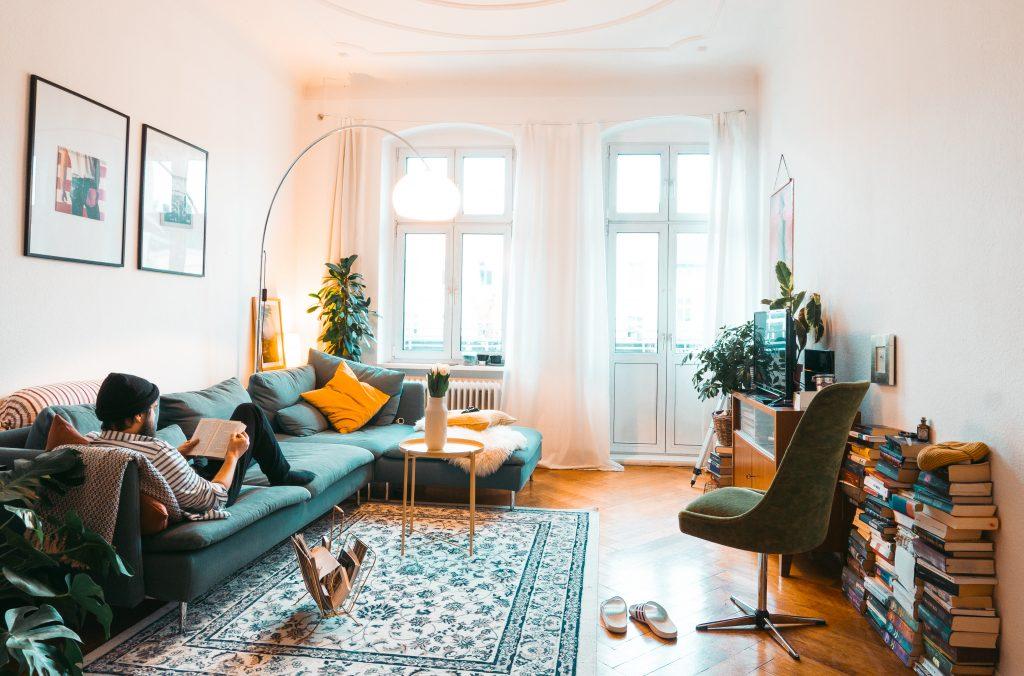 Voll eingerichtetes Wohnzimmer mit Mann, der auf blauer Couch liest, Bücherstapel, Pflanzen und Vintageflair