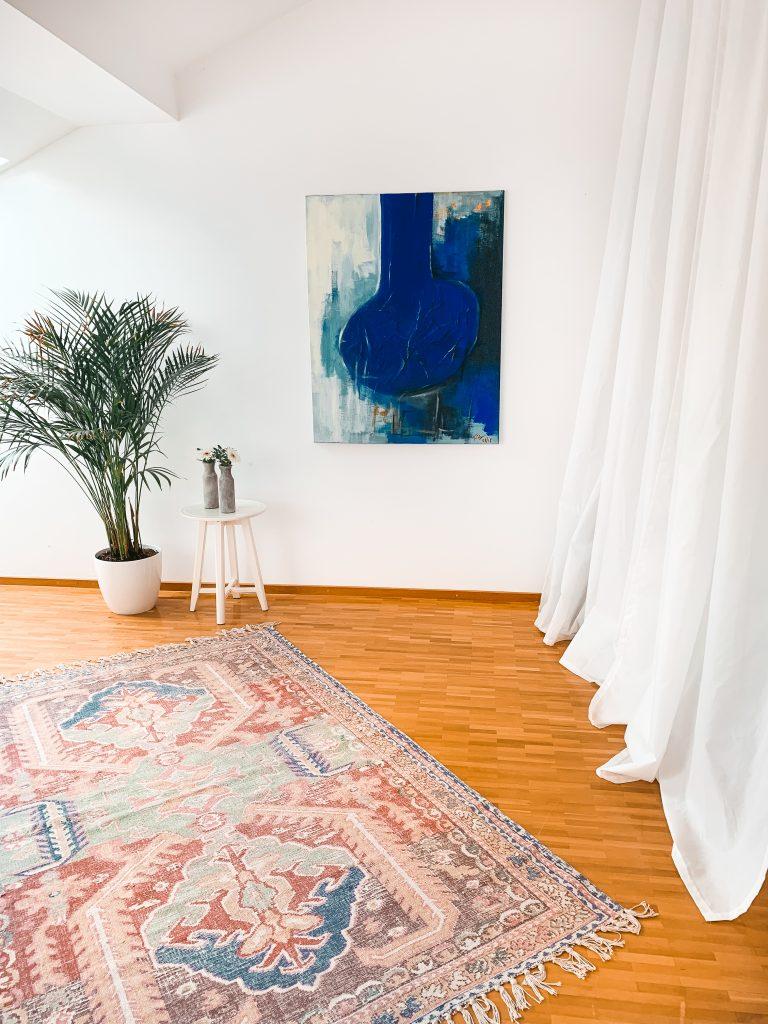 Ausblick in das Schlafzimmer mit blauem, selbstgemalten Bild, orientalischem Teppich, Zimmerpflanze und weißem Vorhang - Der 7. Himmel über Berlin