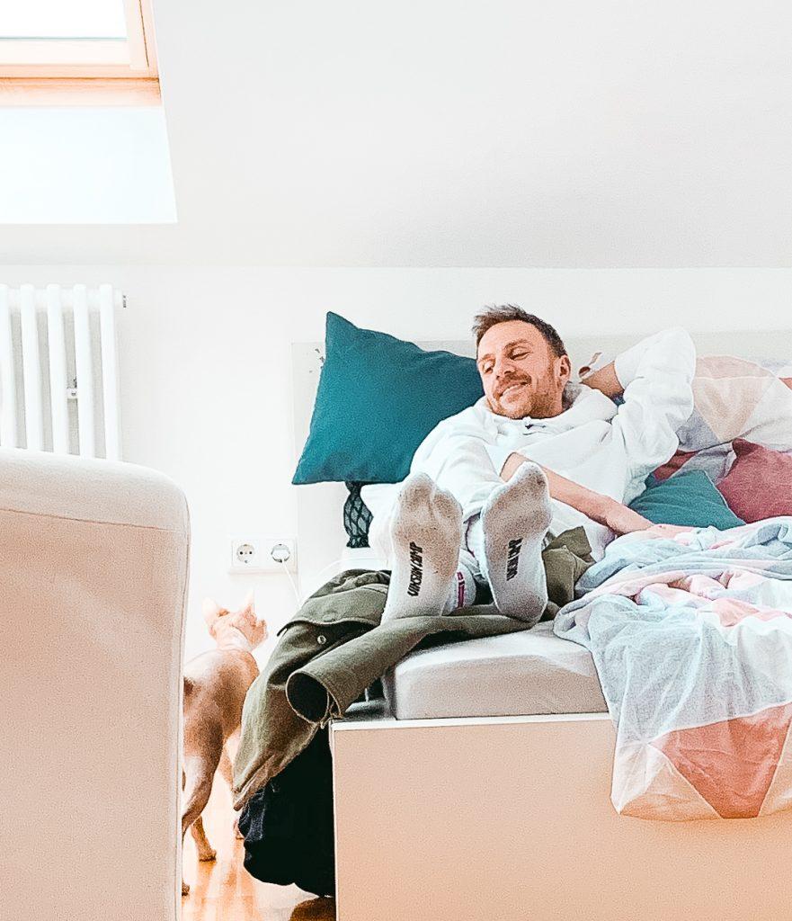 Ein Mann der relaxed und lächelnd im Bett liegt, während er sein Katze beobachtet - Der 7. Himmel über Berlin