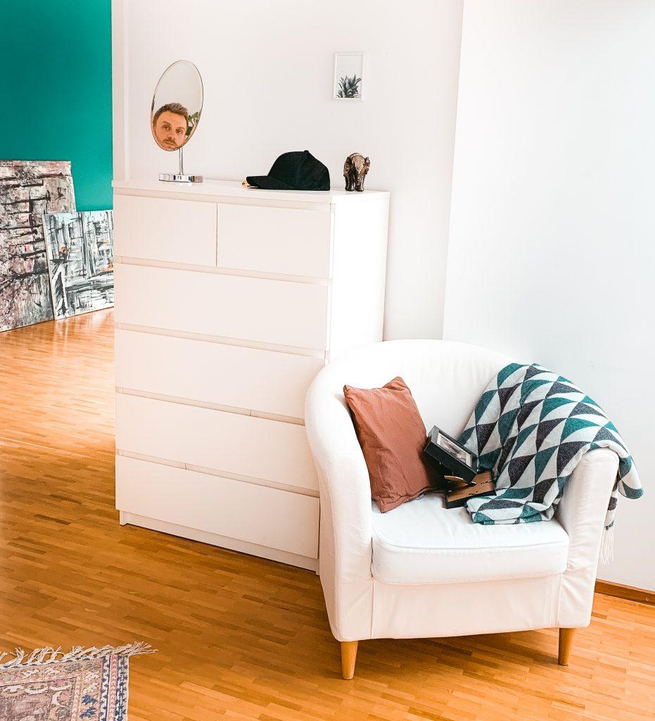 Blick in das Wohnzimmer, mit grüner Wand im Hintergrund, weißem Sessel und Kommode im Vordergrund. Das Gesicht eines Mannes ist im Spiegel zu sehen - Der 7. Himmel über Berlin
