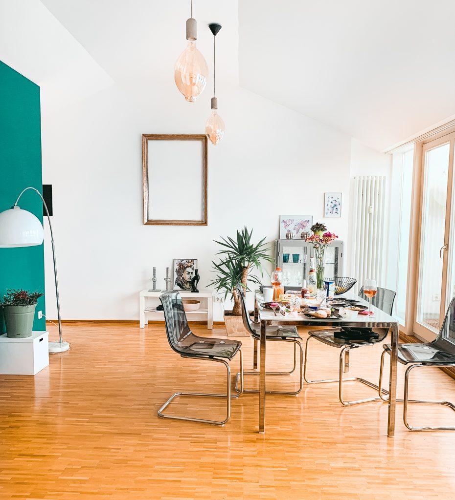 Blick ins Wohnzimmer, links eine grüne Wand, in der Mitte ein gedeckter Frühstückstisch und rechts eine Fensterfront zur Dachterrasse - Der 7. Himmel über Berlin