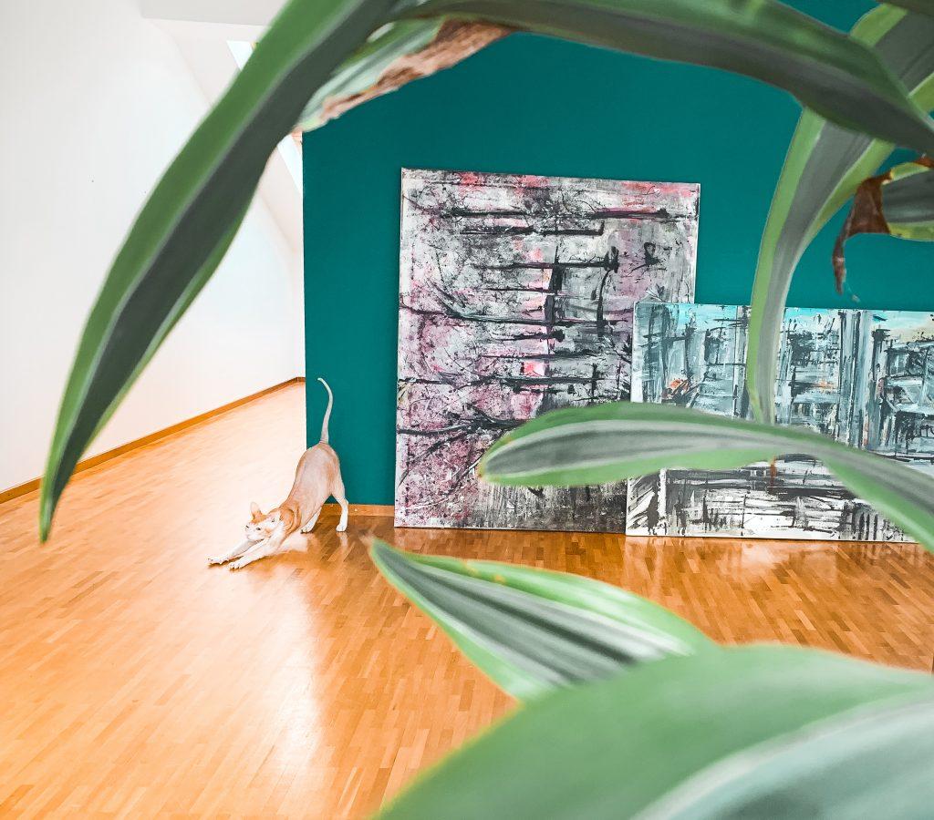 Eine Nacktkatze stretched sich vor einer grünen Wand und neben selbstgemachter Malerei - Der 7. Himmel über Berlin