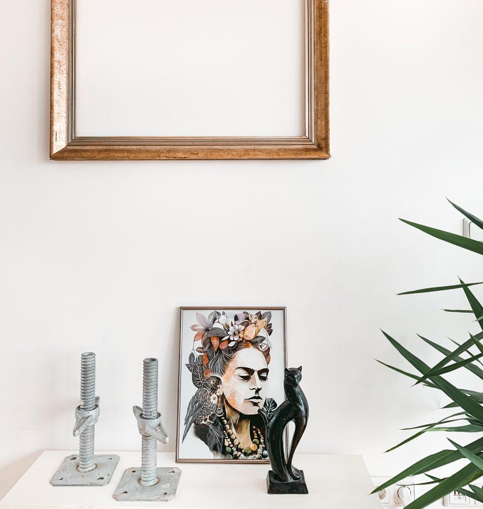 Blick auf die Dekoration. Ein leerer Vintagebilderrahmen und ein moderner Kunstdruck von Frida Kahlo - Der 7. Himmel über Berlin