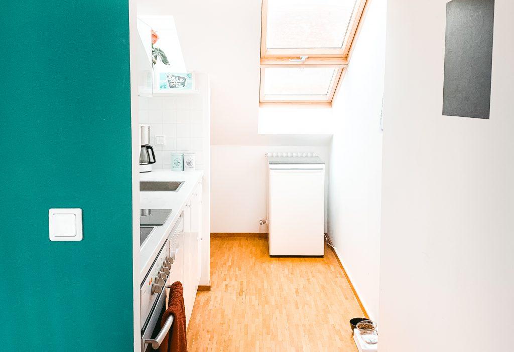 Einblick in die Küchenecke, mit grüner Wand und hellem Interior - Der 7. Himmel über Berlin