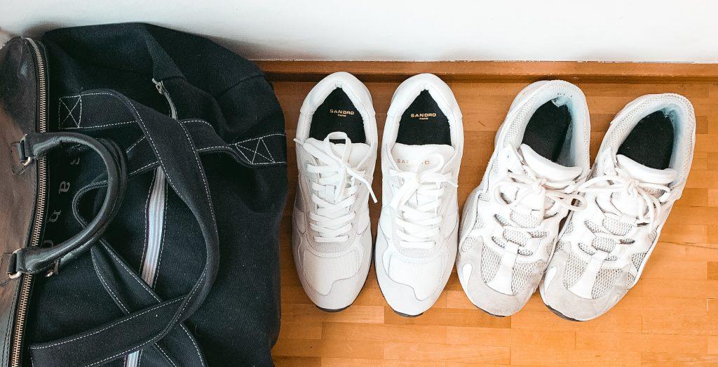schwarze Tasche mit zwei Paar weißer Sneakers ordentlich aufgereiht - Der 7. Himmel über Berlin