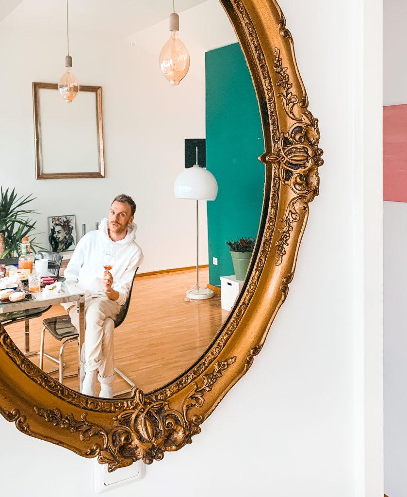 Mann in Antikspiegel gespiegelt, mit einem Glas Sekt in der Hand in seinem Wohnzimmer - Der 7. Himmel über Berlin
