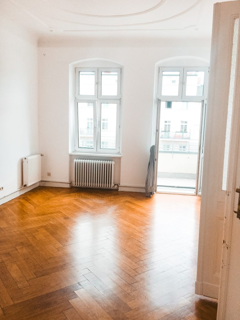 Ein leerer Raum mit Fenster, Dielenboden und offener Balkontür