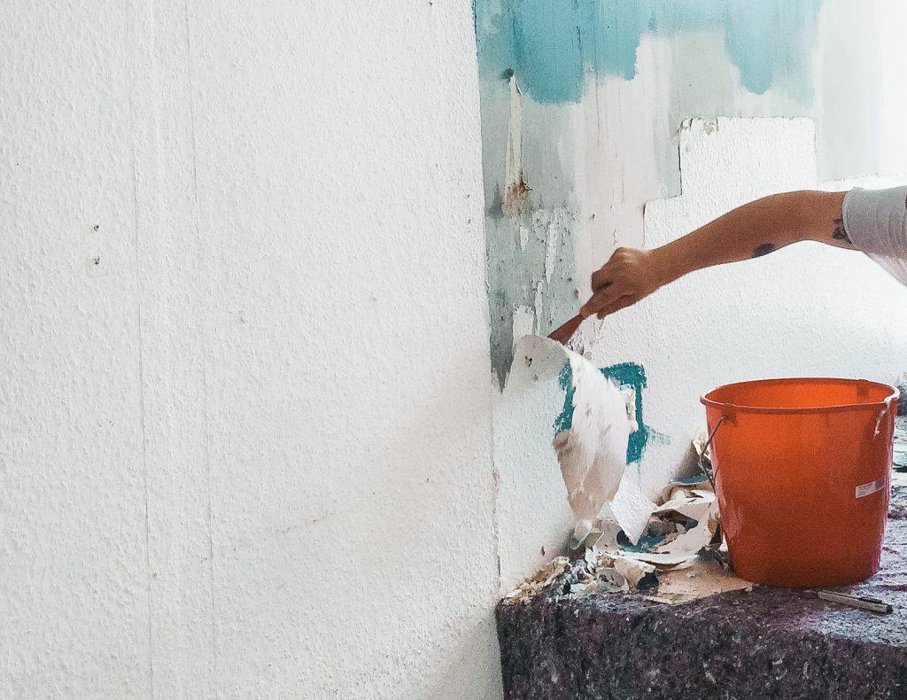 Ein Arm mit Spachtel in der Hand, der Tapete von der Wand abkratzt