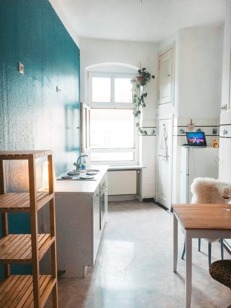 Eine Küche nach dem Umbau mit blauer Wand links und Sitzecke rechts