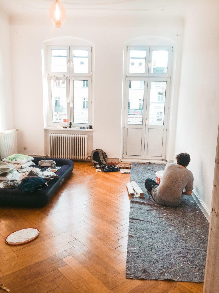Ein leerer Raum mit Fenster, Dielenboden und offener Balkontür, rechts sitzt ein Mann auf einer Streichunterlage, links liegt eine aufblasbare Schlafmatratze