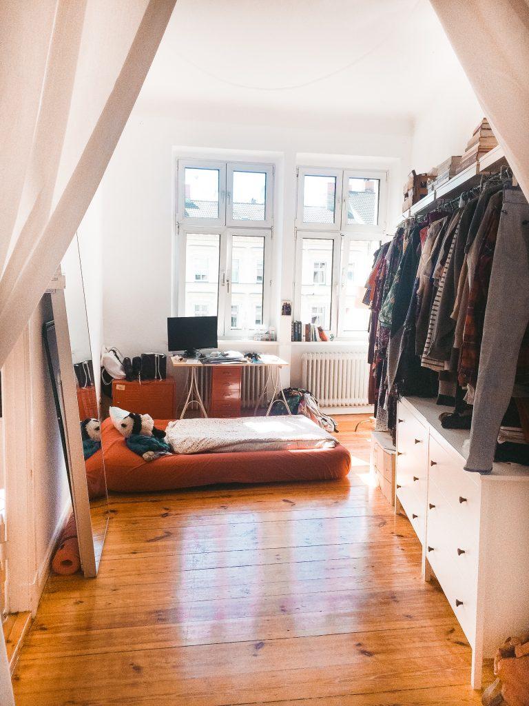 Blick durch Gardine auf einen Raum mit Schreibtisch, Luftmatratze und Garderobe auf rechter Seite