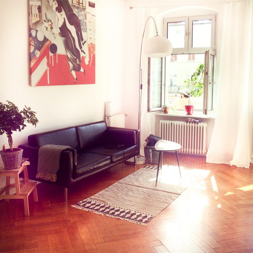 Blick in ein sonniges Wohnzimmer mit Ledersofa unter einem Chagall-Bild, Teppich und Couchtisch. Das Fenster ist offen