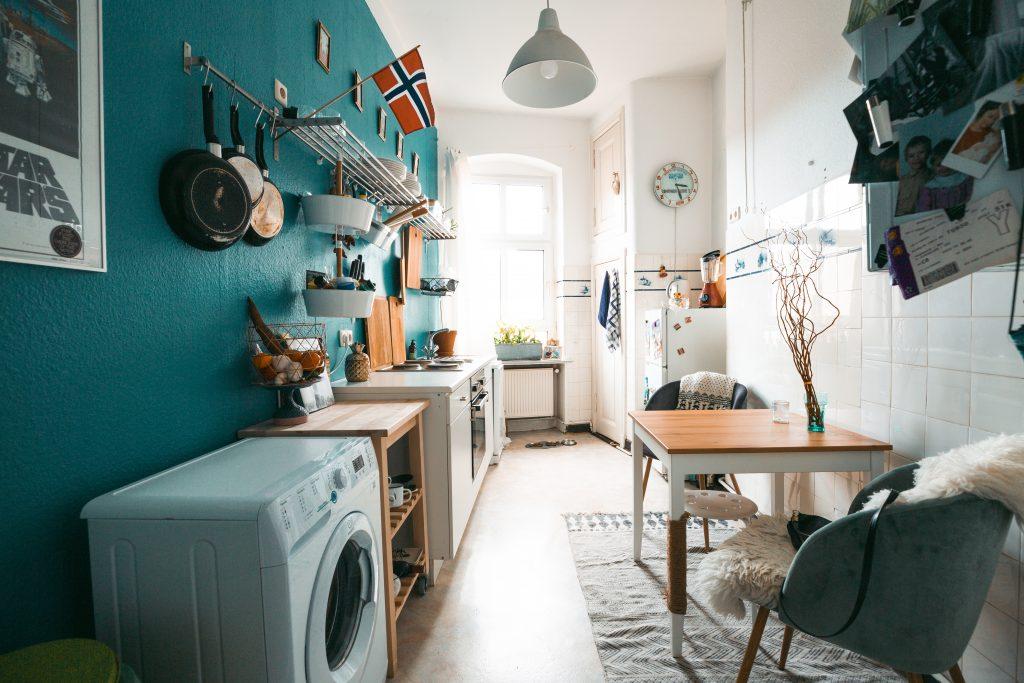 Überblick über eine komplett eingerichtete Küche, mit blauer Wand links, Sitzecke rechts.