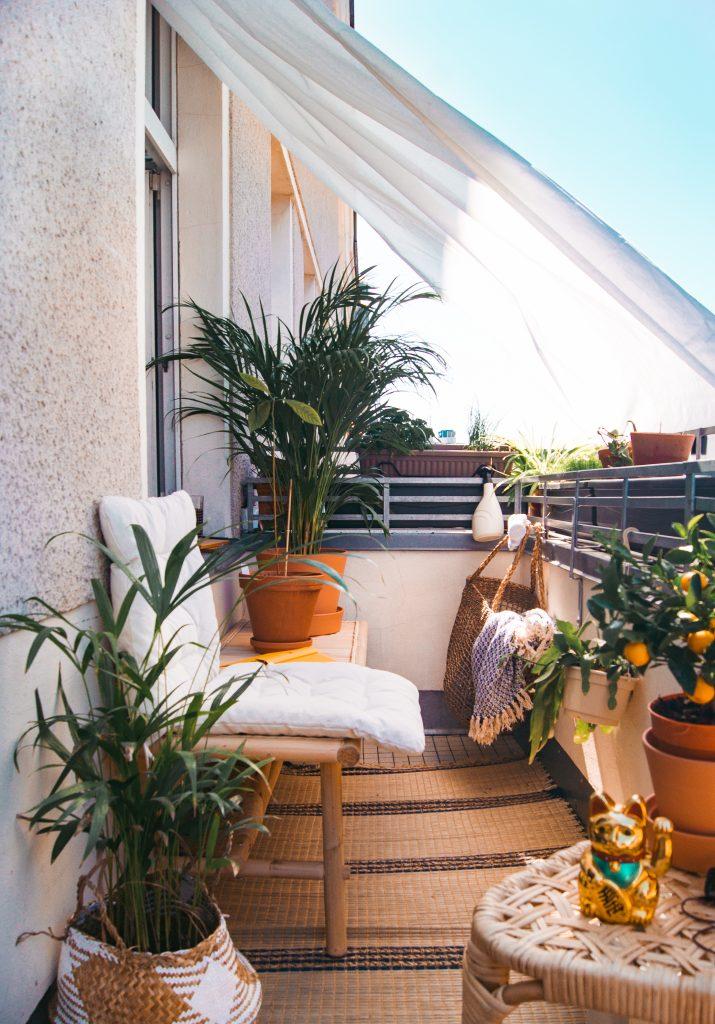 Mit Pflanzen und Naturmaterialien gestylter Balkon mit Sonnensegel