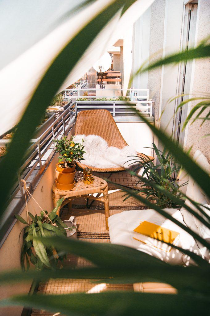 Durch Pflanzen hindurch fotografierter Baststuhl auf Balkon