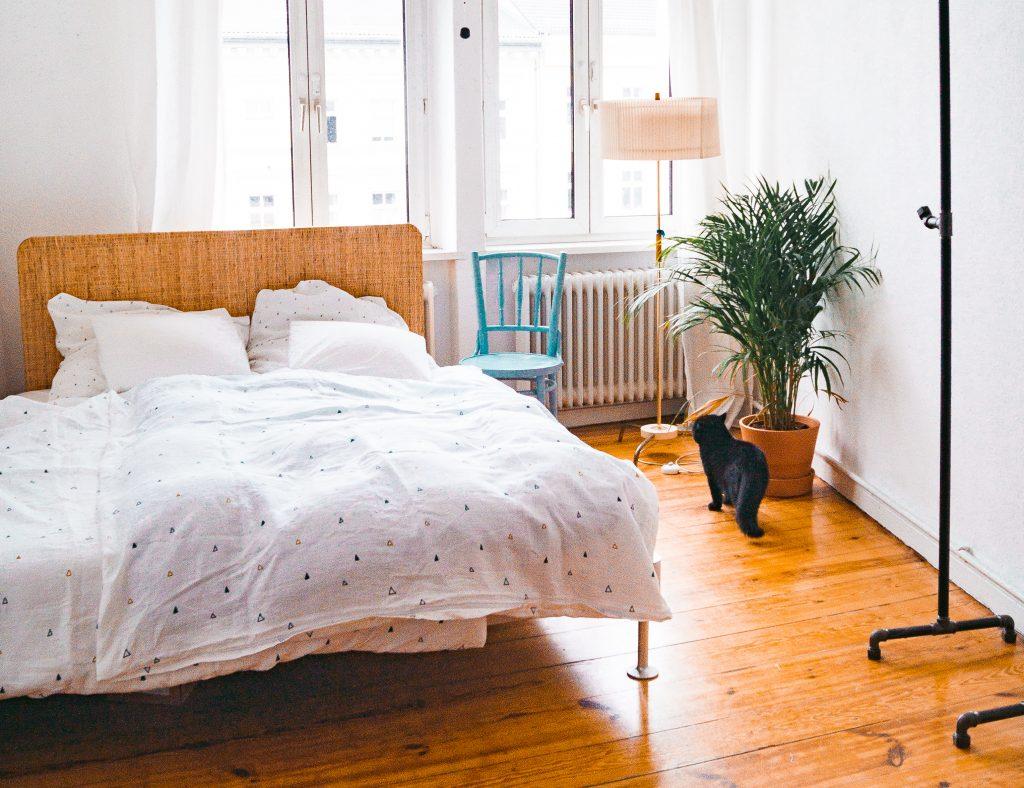 Deko-Tipps zum Wohlfühl-Wohnen - Ikea Delaktig Bett in Altbau-Wohnung mit schwarzer Katze auf Dielenboden. Helle Oyoyo Bettwäsche neben blauem Stuhl und Vintage-Lampe