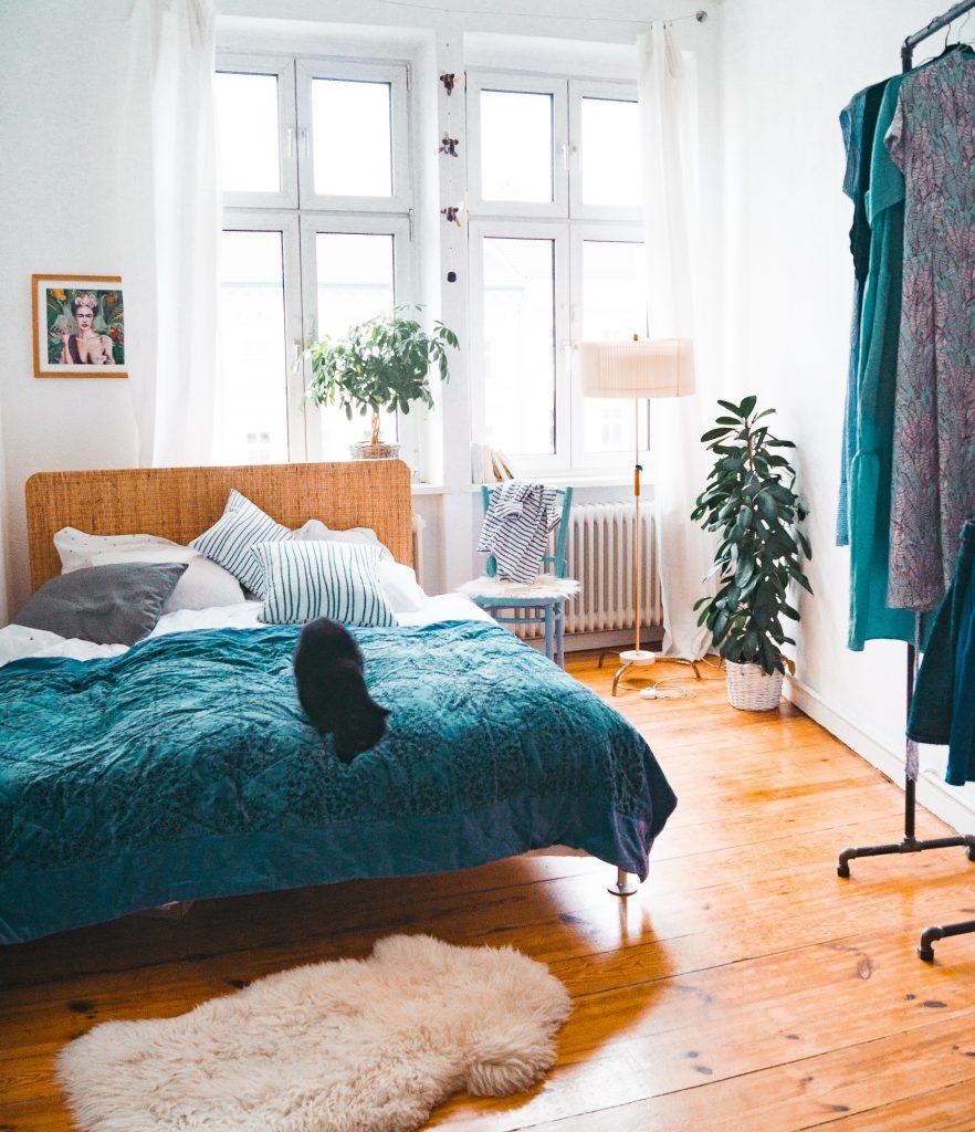 Deko-Tipps zum Wohlfühl-Wohnen - Ikea Delaktig Bett zusammen in blauer Deko in Altbau mit Dielenboden und schwarzer Katze auf der Tagesdecke