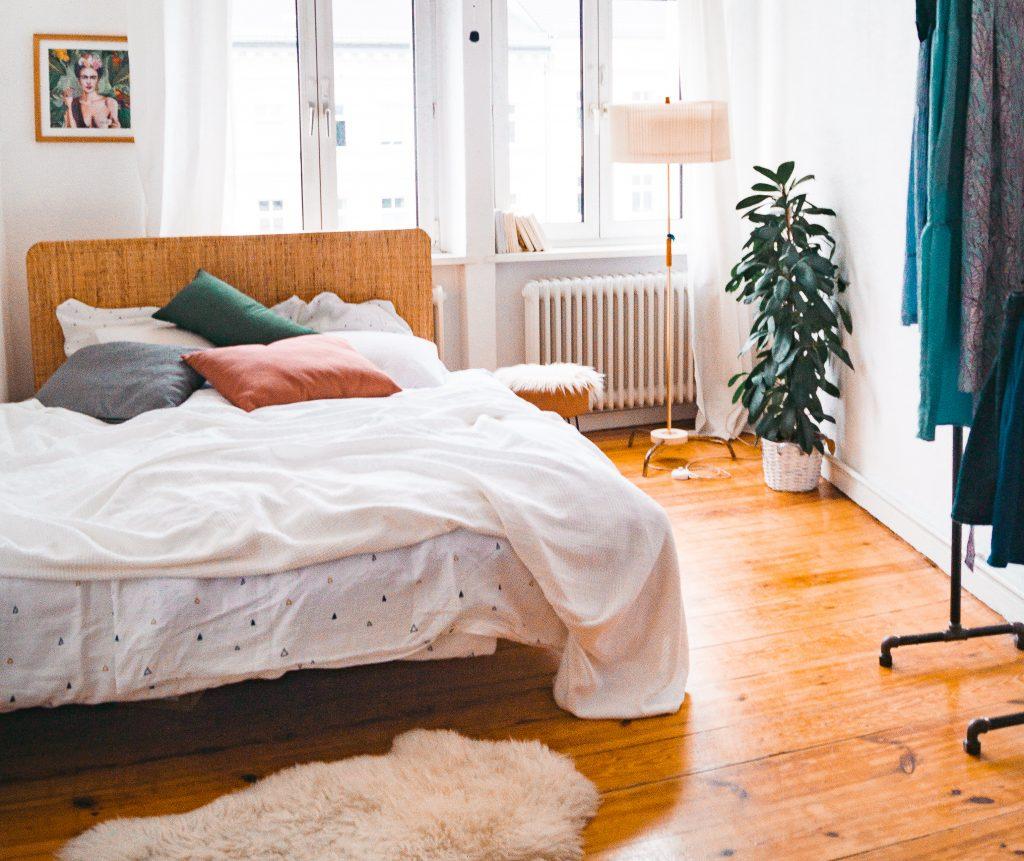 Deko-Tipps zum Wohlfühl-Wohnen - Ikea Delaktig Bett in Altbauwohnung mit Dielenboden, Vintage-Lampe und farbigen Kopfkissen. Frida Kahlo Bild an der Wand und Leder Hocker von Maison du Monde