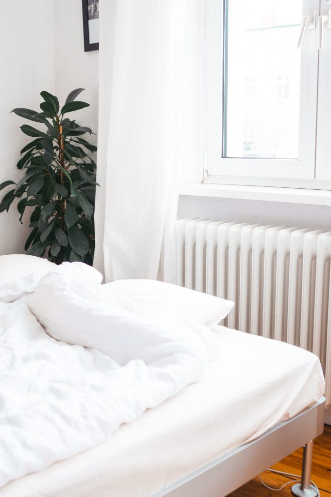 Schlichte, weiße H&Mhome Bettwäsche auf Ijea Delaktig Bett in Altbau mit Dielenboden