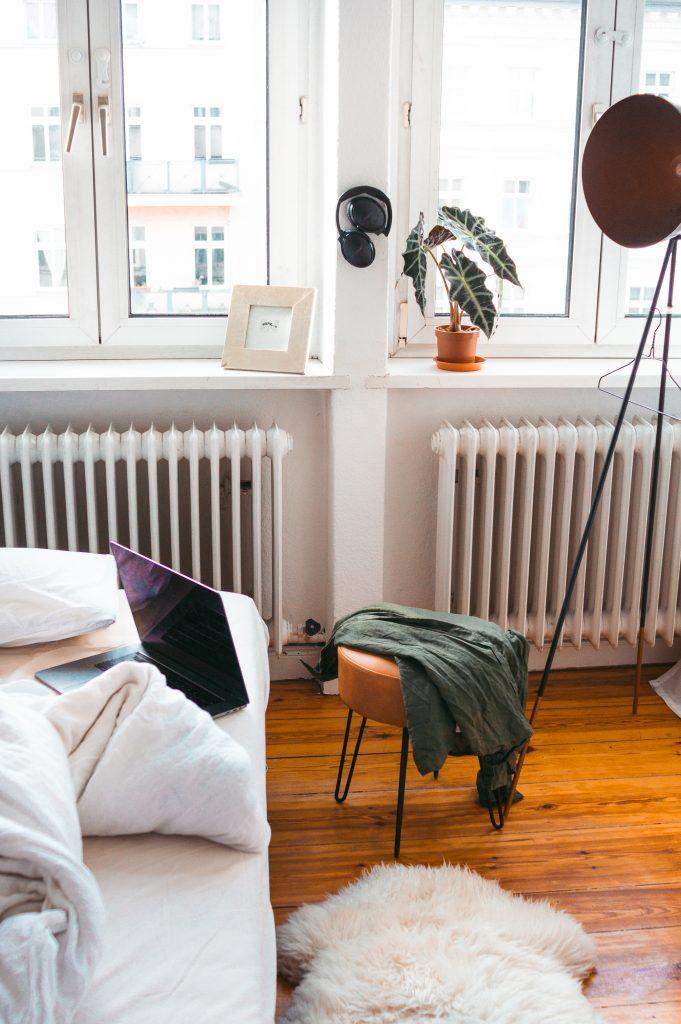 Deko-Tipps zum Wohlfühl-Wohnen - Detailaufnahme Ikea Delaktig Bett mit Maison du Monde Lederhocker, Apple Macbook und Bauhaus Strahler