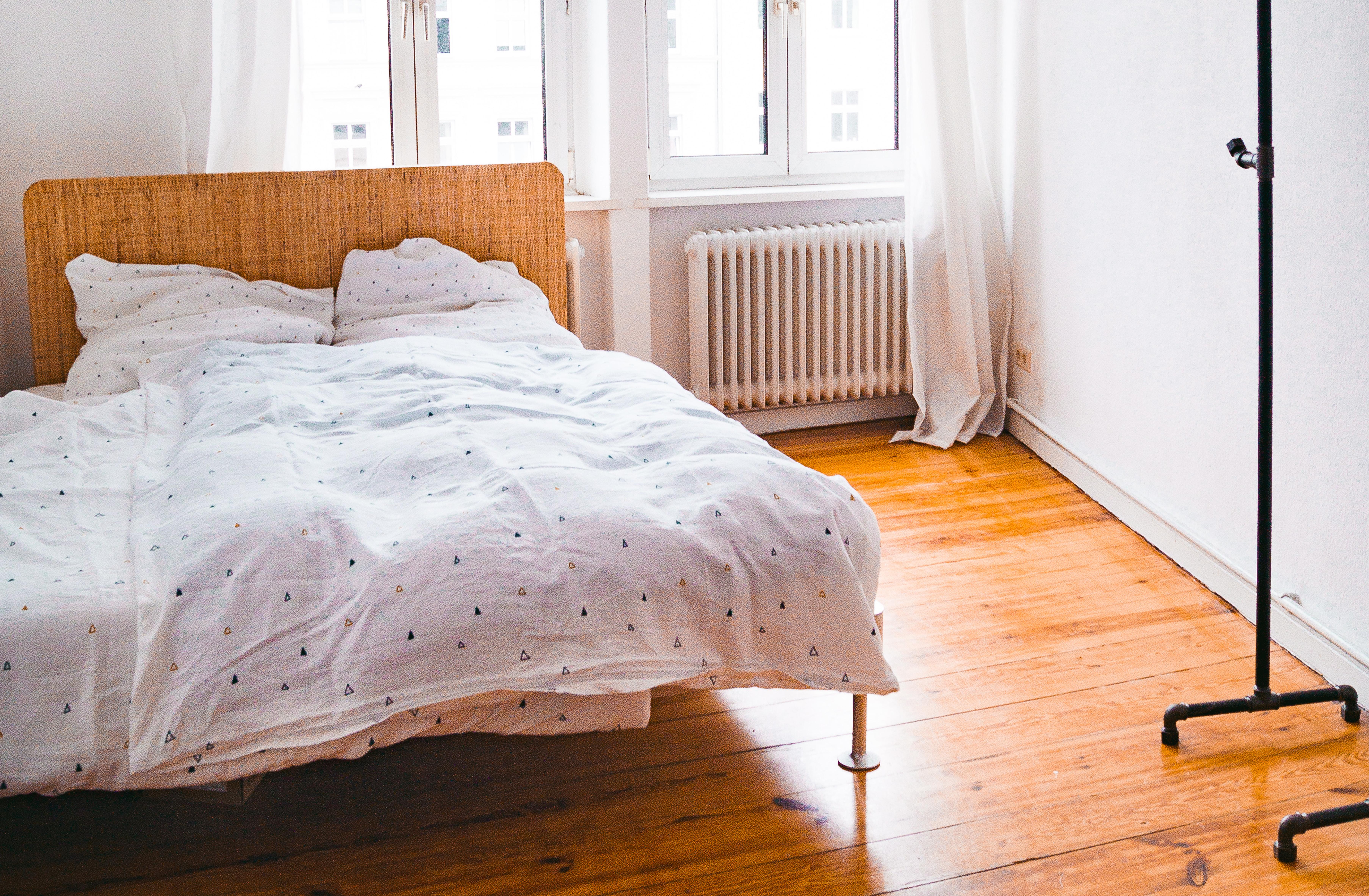 Ikea Delaktig Bett in Altbau-Wohnung mit hellem Interior, Dielenboden und Rackbuddy Kleiderstange