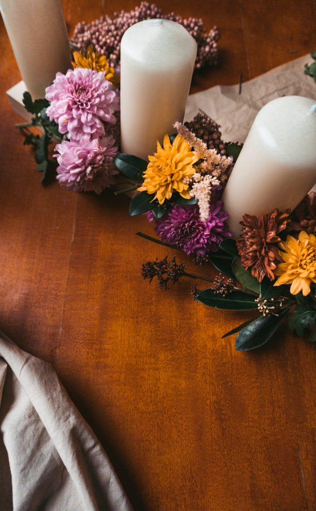 Fridlaa bastelt einen unkonventionellen Adventskranz  im Hintergrund liegt florale Dekoration im Vordergrund steht der dekorierte Adventskranz