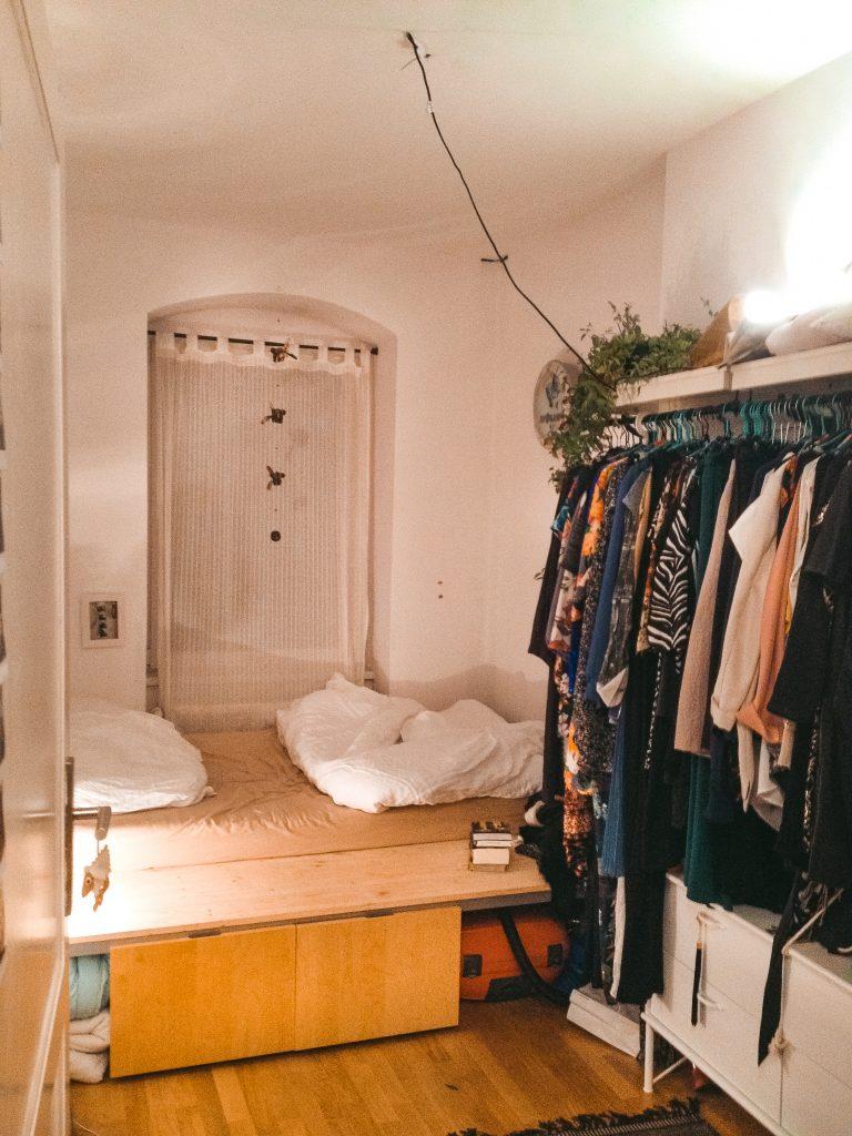 Fridlaas Mini-Schlafzimmer mit Bett und offenem Kleiderschrank in ihrer kleinen ersten Wohnung Berlin mit 1,5 Zimmern